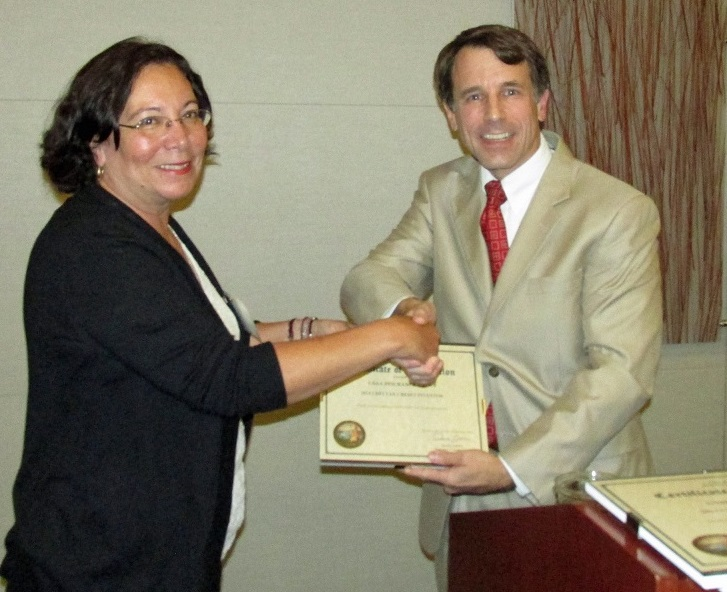 Diane Giampaoli, on behalf of CSAA, accepting a COIN CDFI Tax Credit Award from the Commissioner.