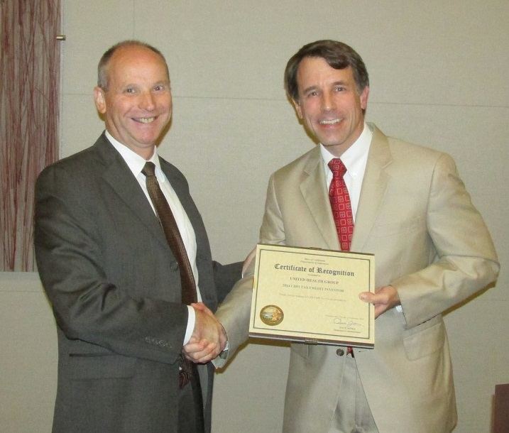 Steven Henry, on behalf of UnitedHealthcare, accepting a COIN CDFI Tax Credit Award from the Commissioner.