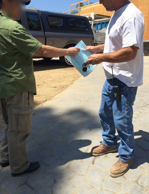 CDI investigator handing out educational materials to contractor